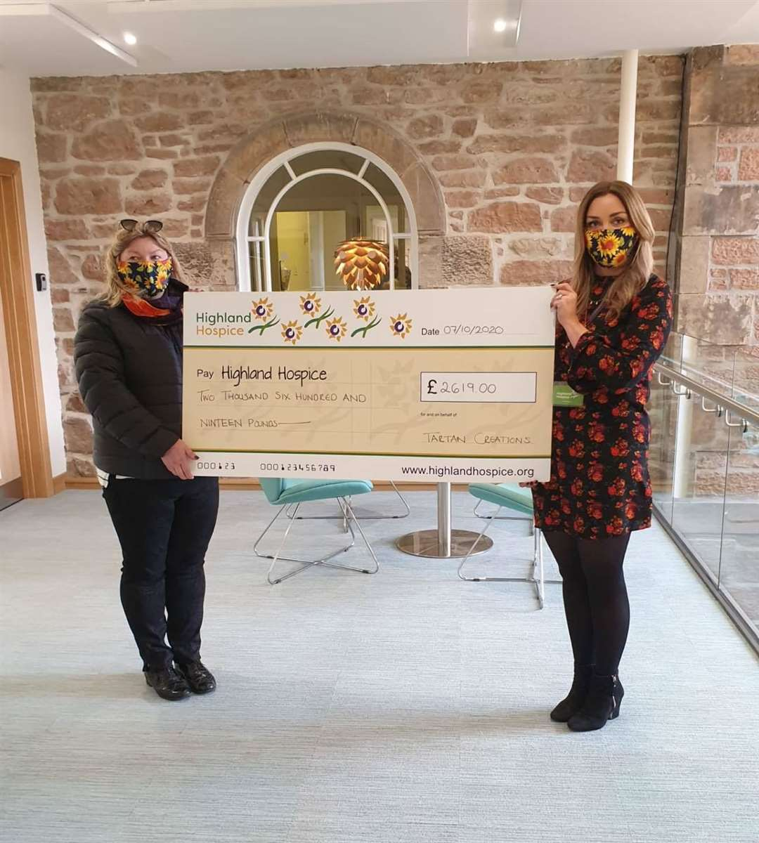 Yvonne Macrae hands her face covering cheque to Emma Nicol of Highland Hospice.