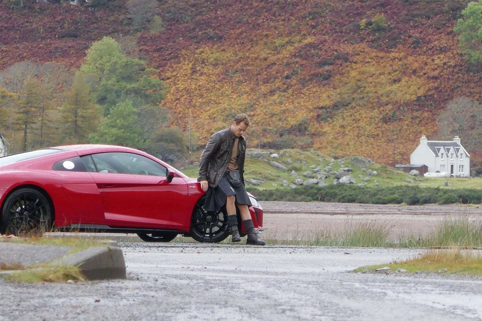 Mr Heughan took time to relax on the bonnet of his car.